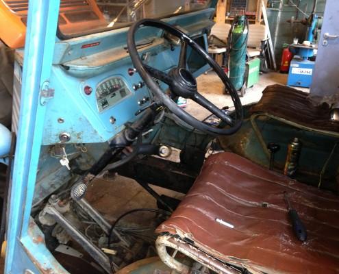 cabine van de auto met kapotte stoelzittingen en motor eruit